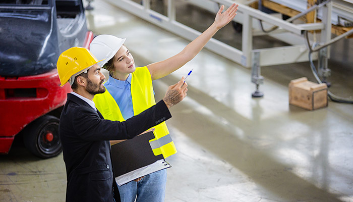 man and woman wearing hardhats in a warehouse or factory, looking and pointing in upwards angle